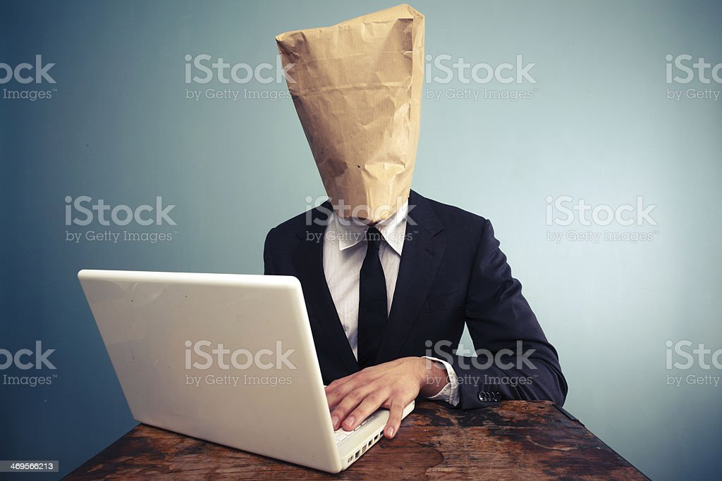 Businessman with bag over head working on computer stock photo