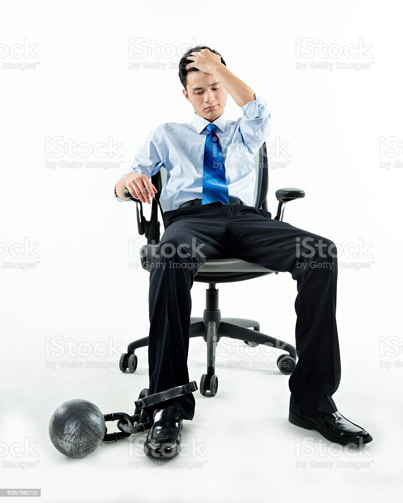 Businessman with ball and chain against white background stock photo