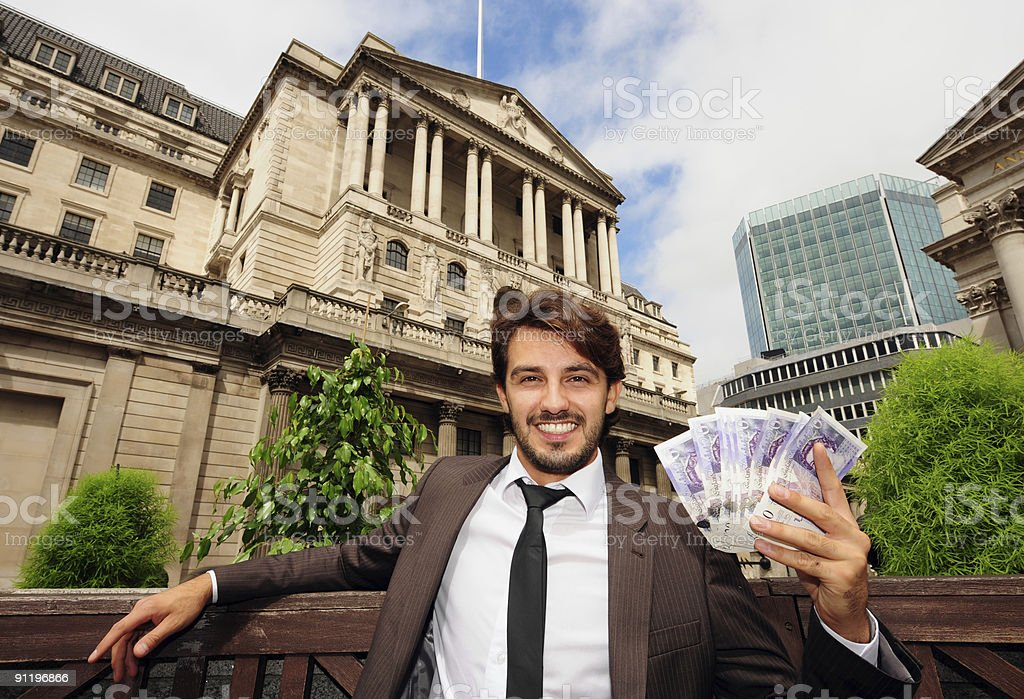 Businessman with Bank of England on the background stock photo