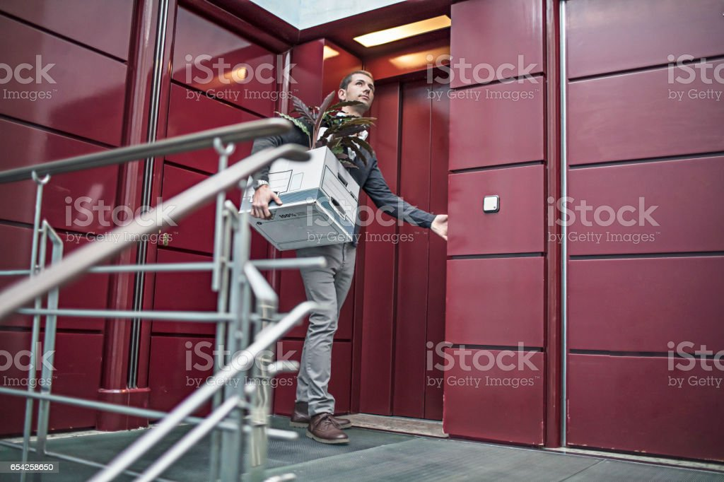 Businessman with belongings at elevator in office stock photo