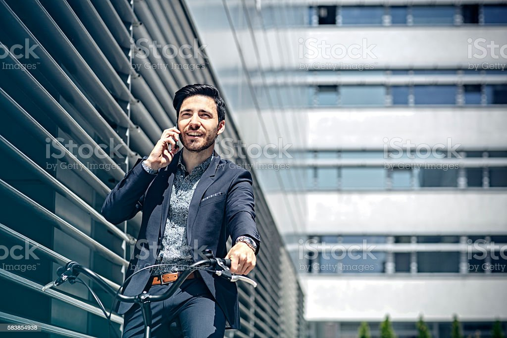 Businessman with bicycle talking on cell phone stock photo