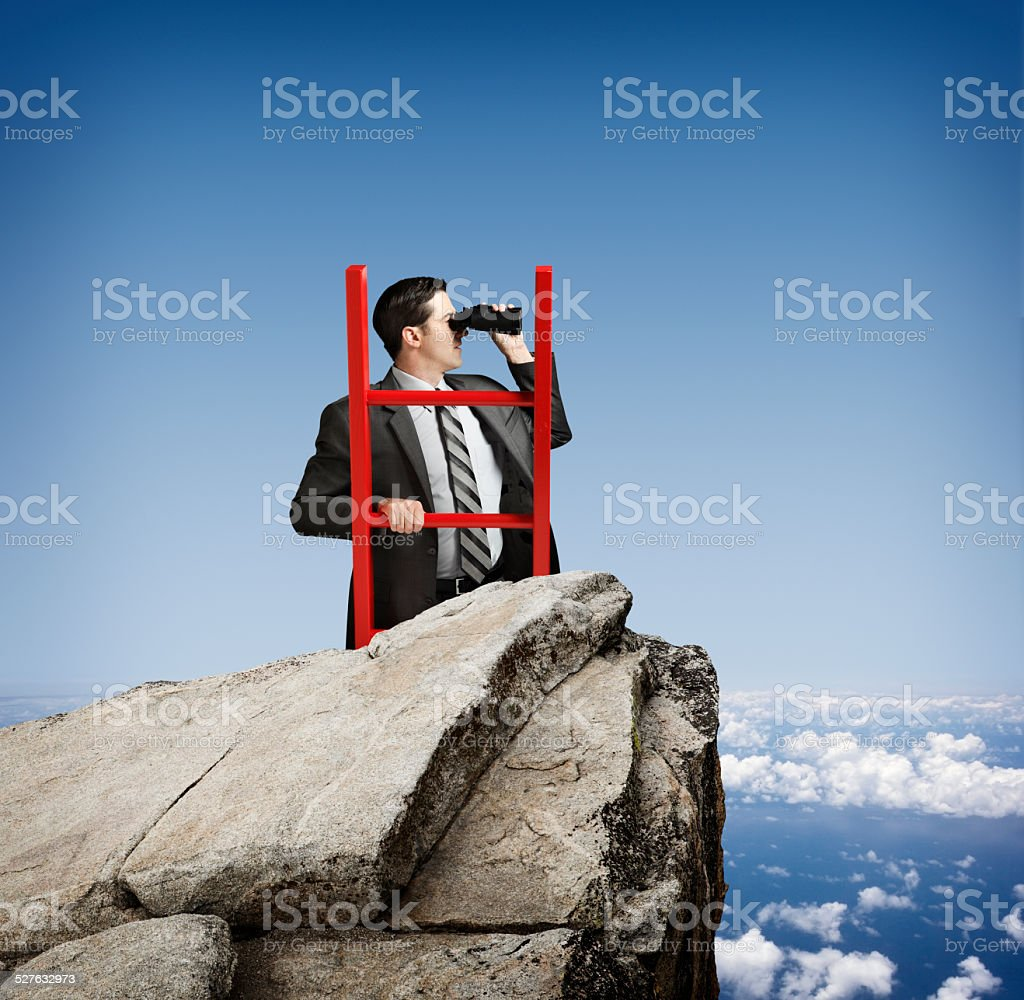 Businessman With Binoculars At Top Of Ladder Looking Into Distance stock photo