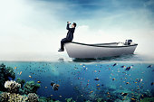 Businessman with binoculars on boat