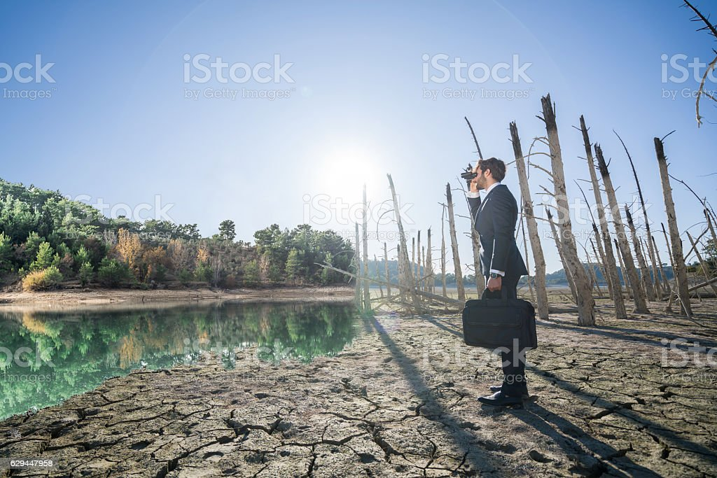 Businessman with binoculars standing on cracked earth stock photo