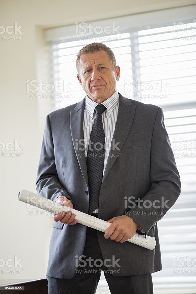 Businessman With Blueprint In Office royalty-free stock photo