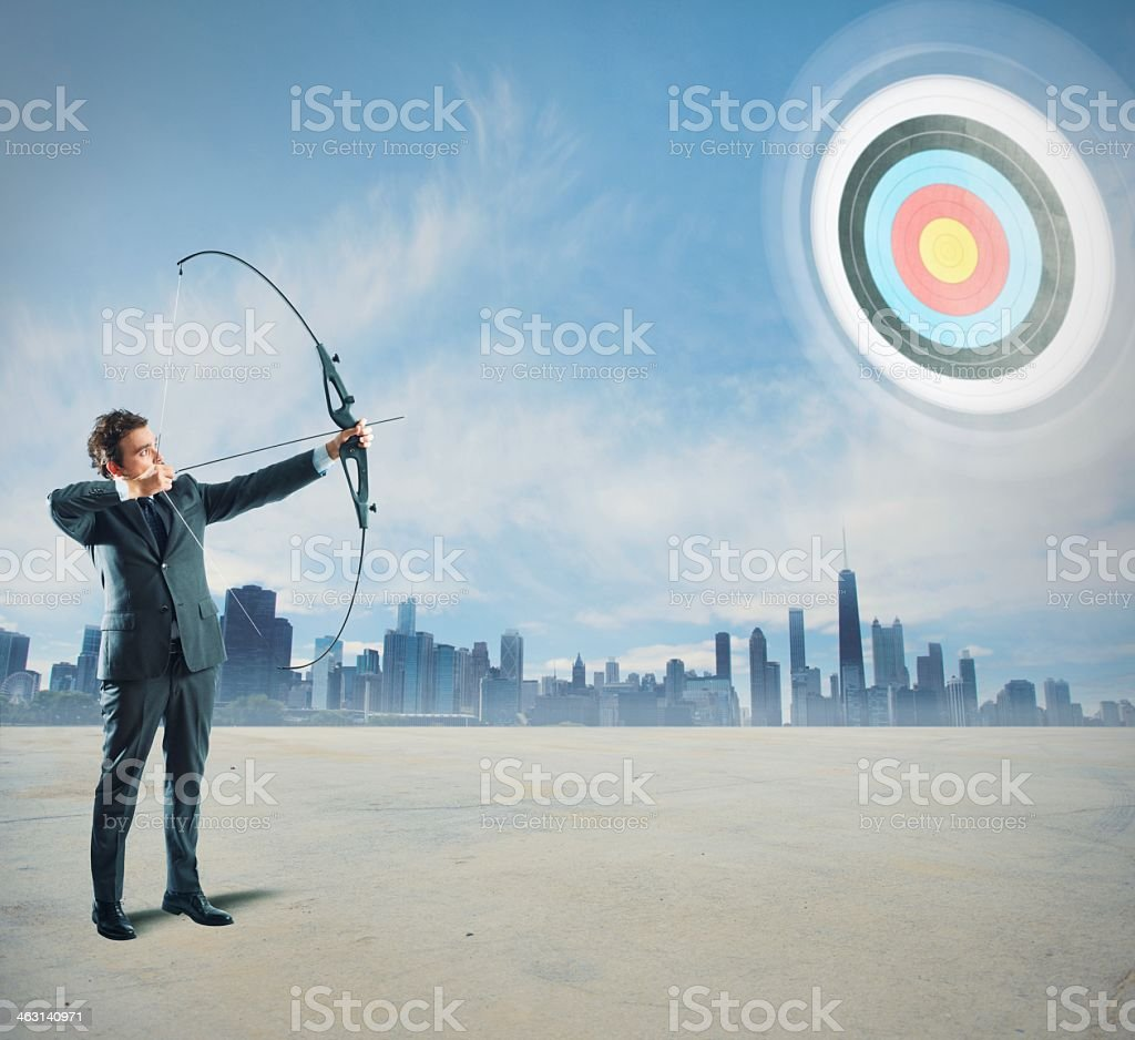 Businessman with bow and arrow pointing to a bullseye in sky stock photo