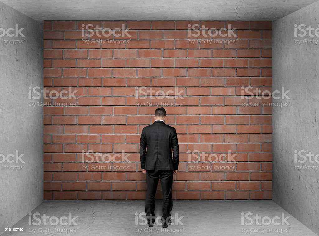 Businessman with bowed head stands front of a brick wall stock photo