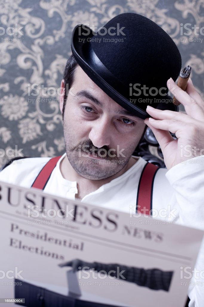 Businessman with bowler hat reading newspaper stock photo