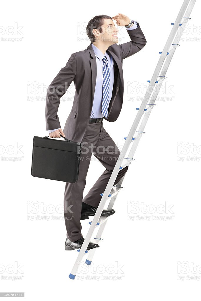 Businessman with  briefcase climbing a ladder stock photo