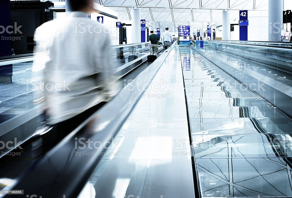 Businessman with briefcase on walkway in airport royalty-free stock photo