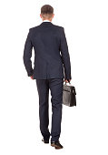 Businessman with briefcase walking away on white