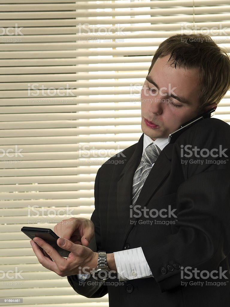 Businessman with calculator talking phone royalty-free stock photo