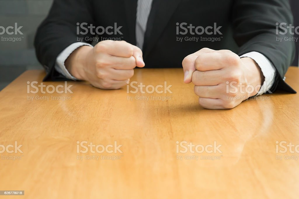 Businessman with clenched fist on the desk , Angry concept stock photo