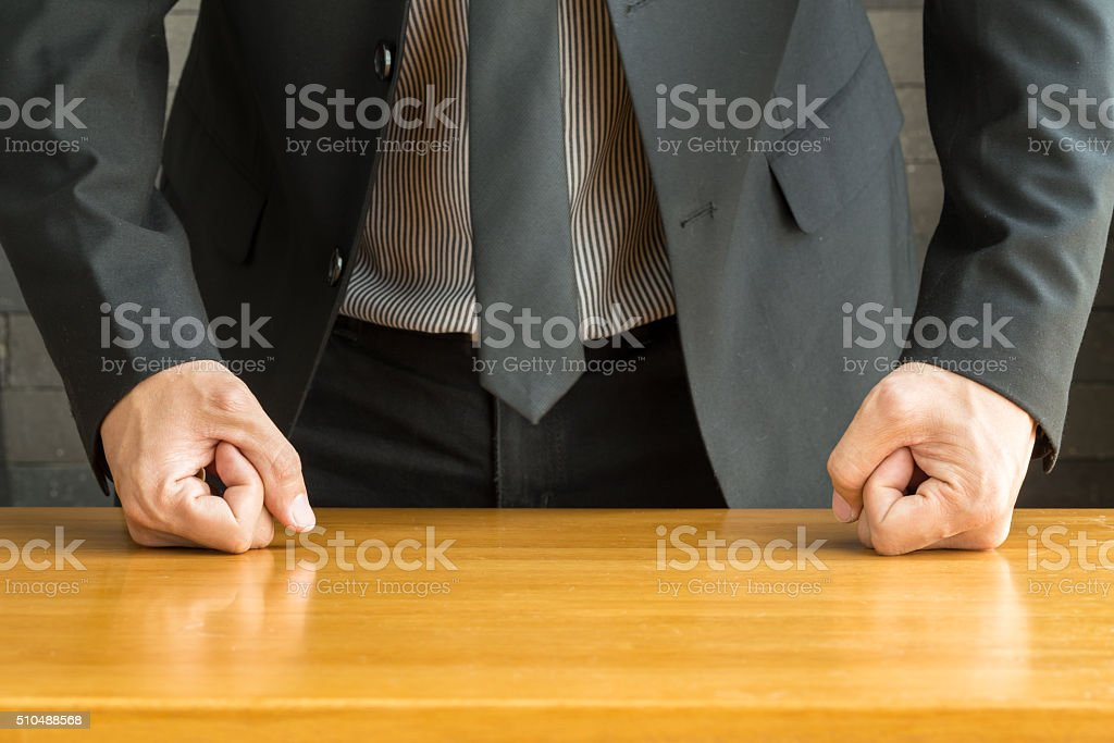 Businessman with clenched fist on the desk at office stock photo