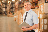 Businessman with clipboard in warehouse