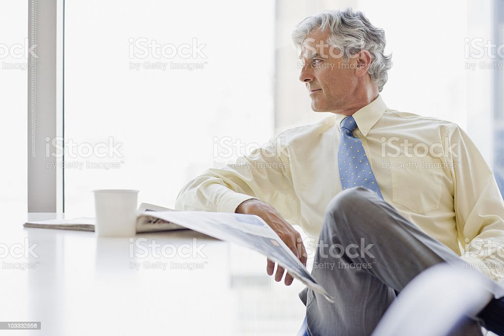 Businessman with coffee and newspaper looking away stock photo
