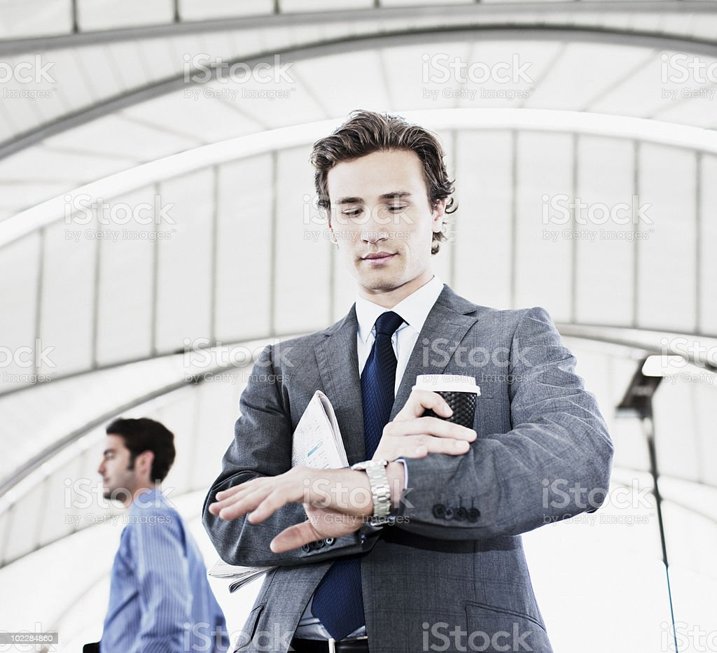 Businessman with coffee checking the time royalty-free stock photo