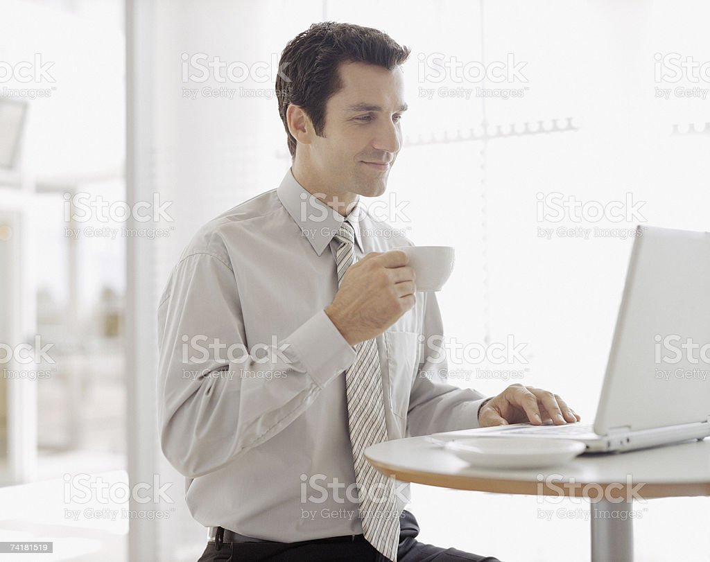 Businessman with coffee cup and laptop royalty-free stock photo