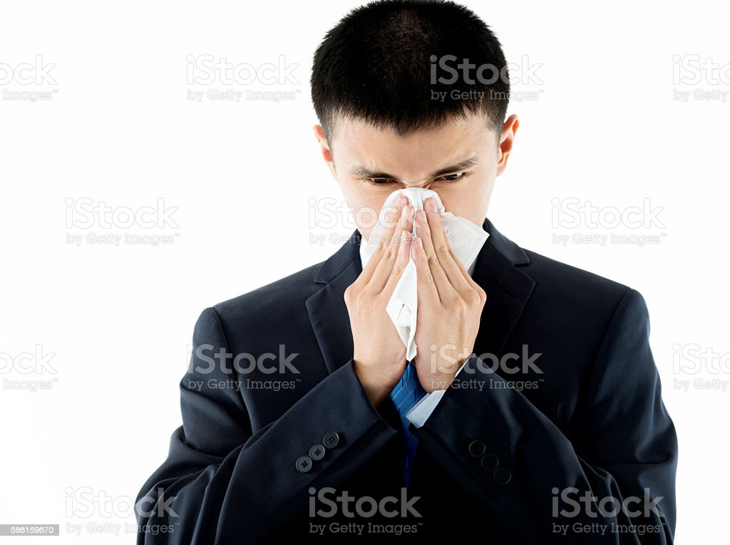 Businessman with cold blowing nose stock photo