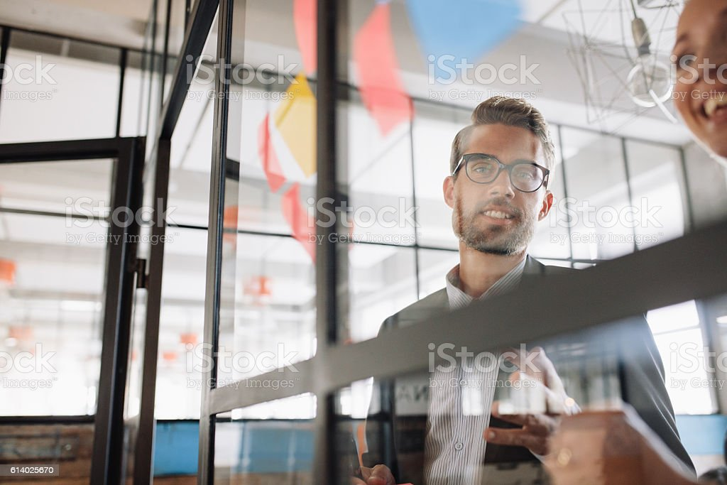 Businessman with colleague looking at adhesive notes stock photo