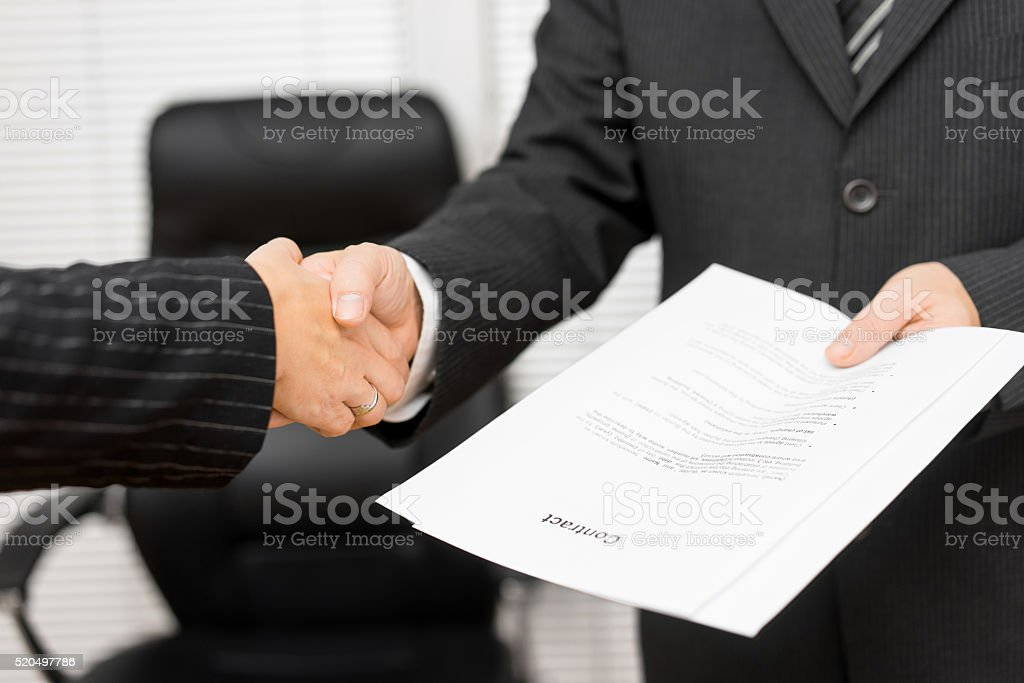 Businessman with contract in his hand is handshaking with businesspartner stock photo