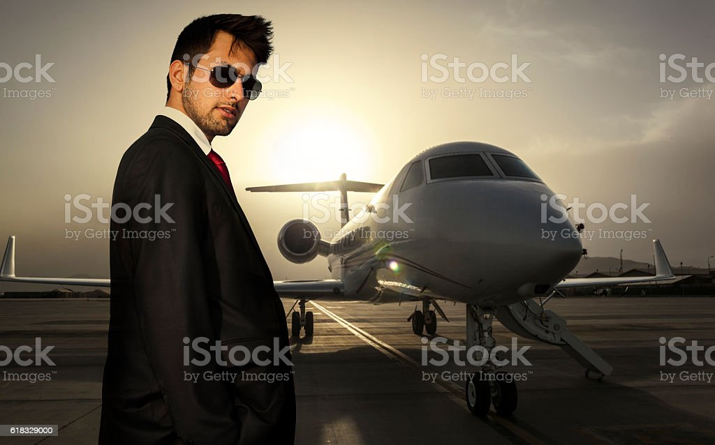 Businessman with corporate jet in background stock photo