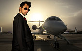 Businessman with corporate jet in background
