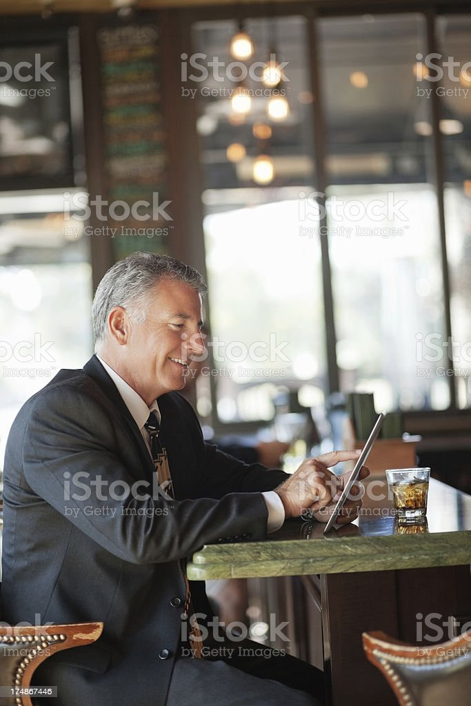 Businessman With Digital Tablet And Drink At Bar Counter royalty-free stock photo