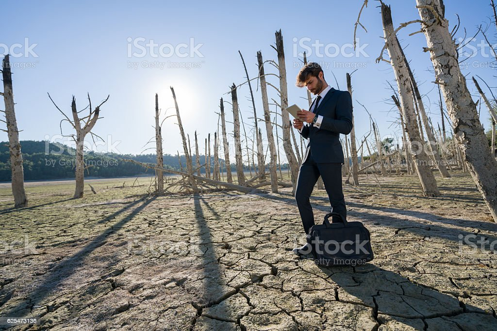 Businessman with digital tablet working on cracked earth stock photo