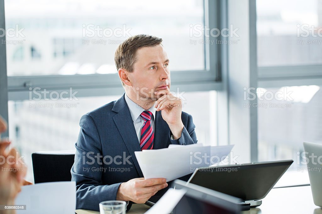 Businessman with documents in meeting at boardroom stock photo