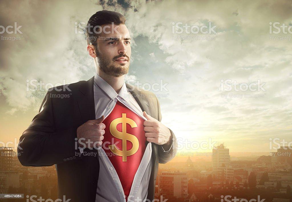 Businessman with dollar sign as superhero stock photo