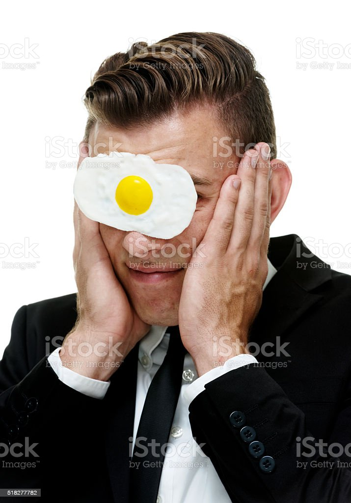 Businessman with egg on his face stock photo