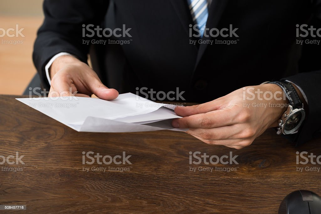 Businessman With Envelopes At Desk stock photo