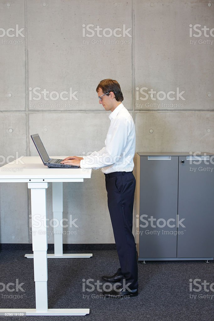 Businessman with eyeglasses standing at height adjustment table stock photo