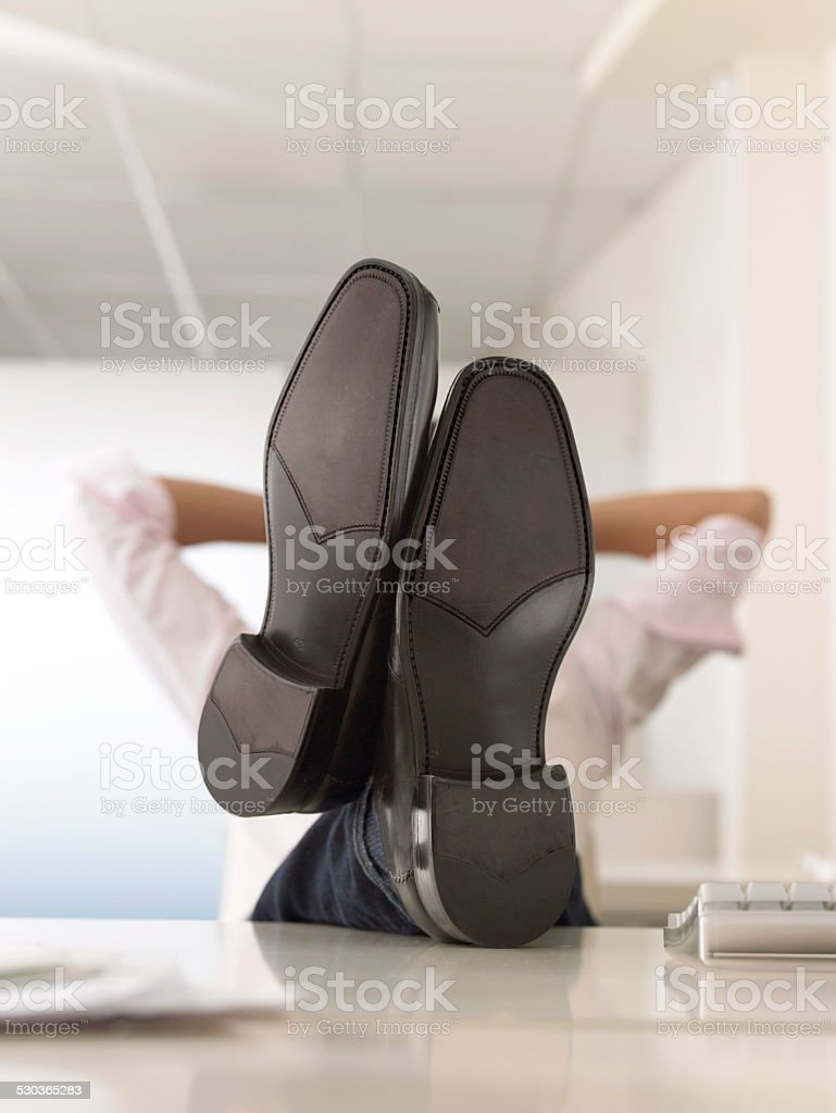 Businessman With Feet Up On Desk stock photo