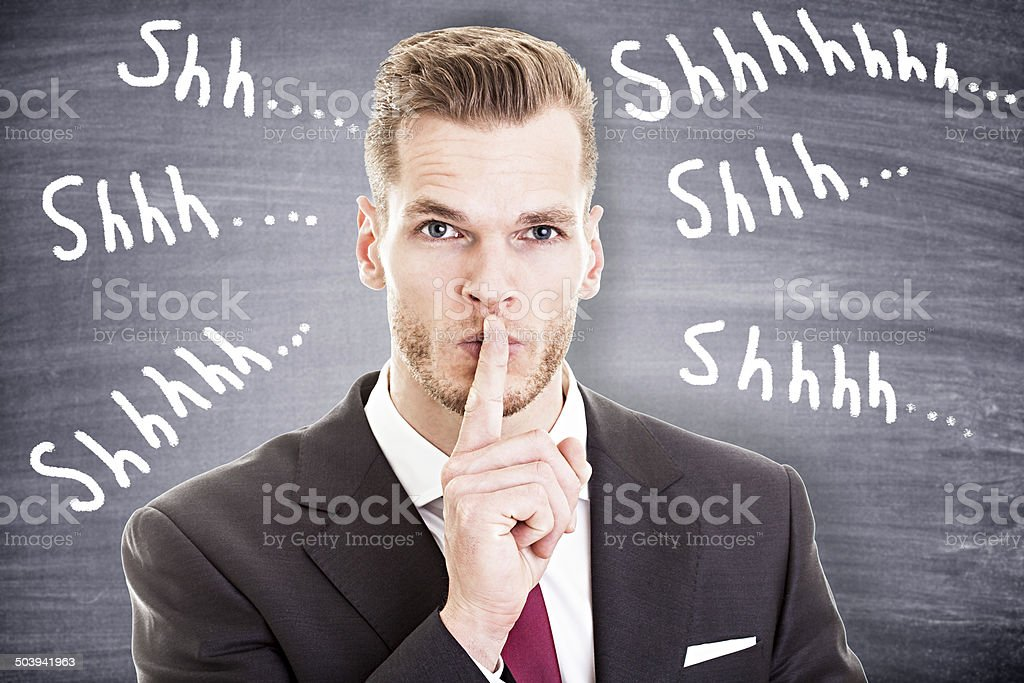 Businessman with finger on lips asking for silence stock photo