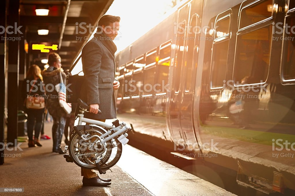 Businessman with folding cycle boarding train stock photo