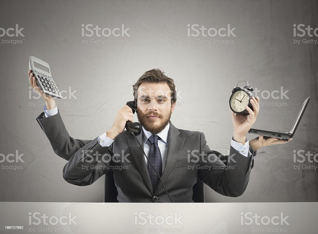 Businessman with four arms and different items multitasking stock photo