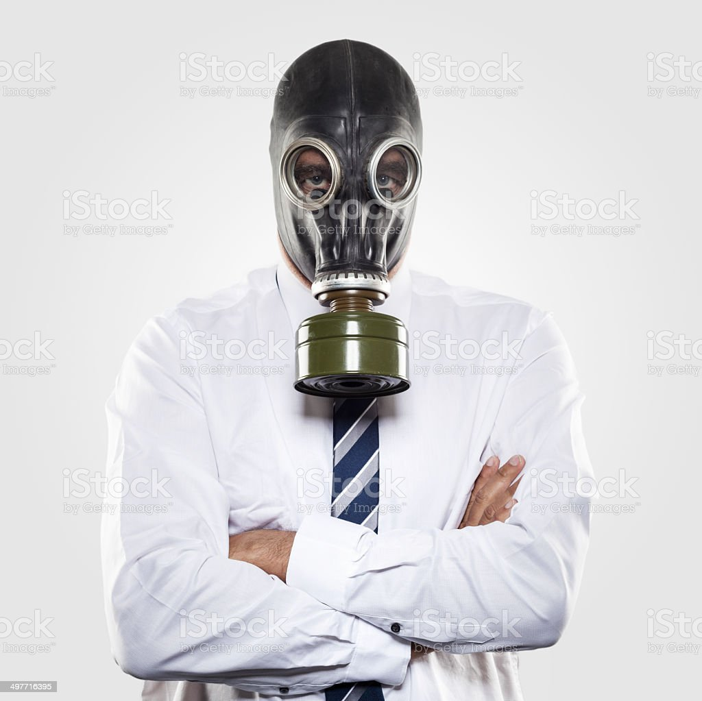 Businessman with gas mask - arms crossed stock photo