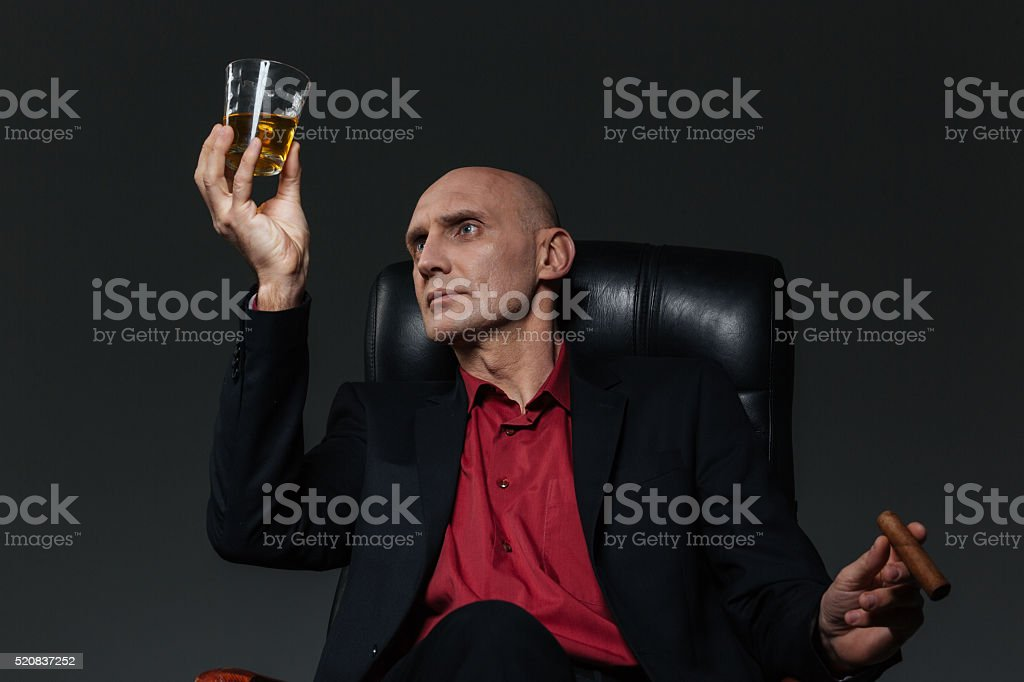 Businessman with glass of whiskey and cigar sitting in chair stock photo