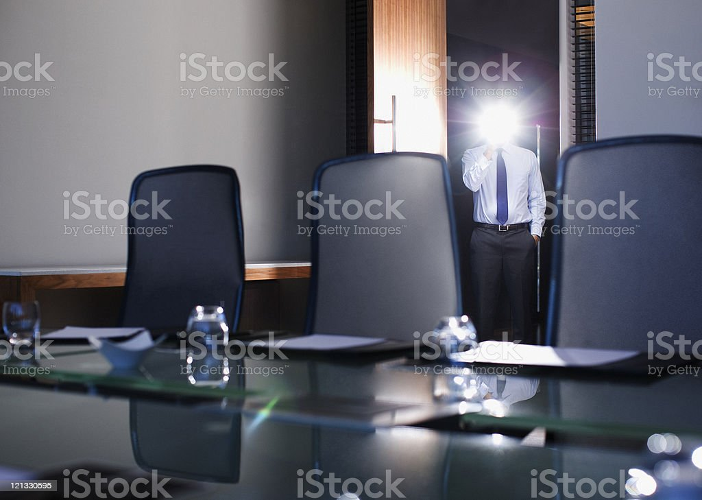 Businessman with glowing light in conference room royalty-free stock photo