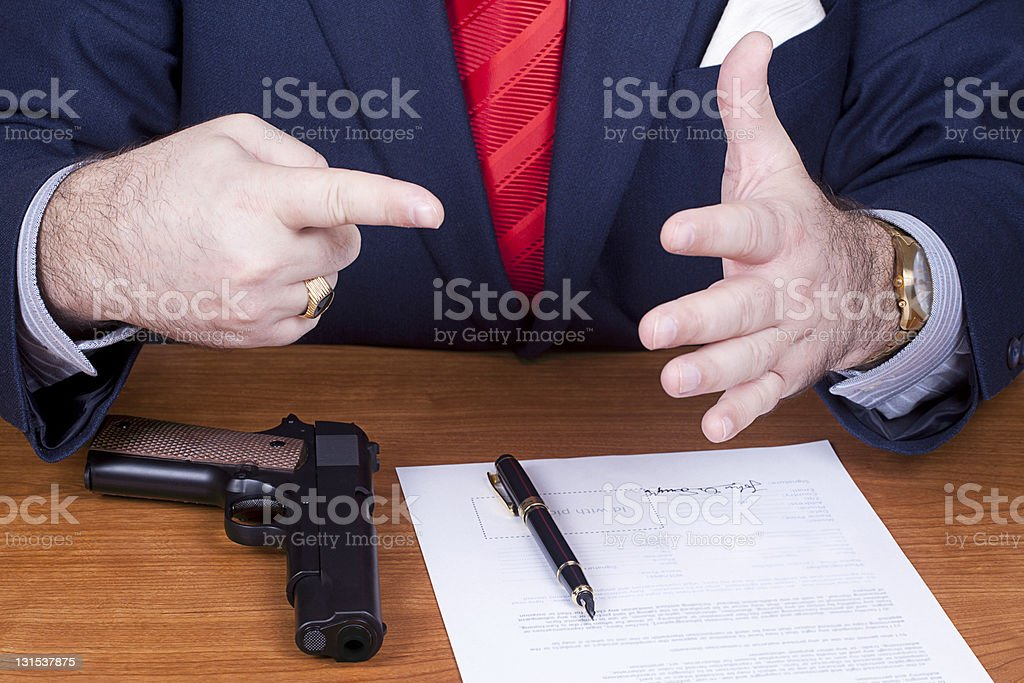 Businessman with gun signing a contract. royalty-free stock photo