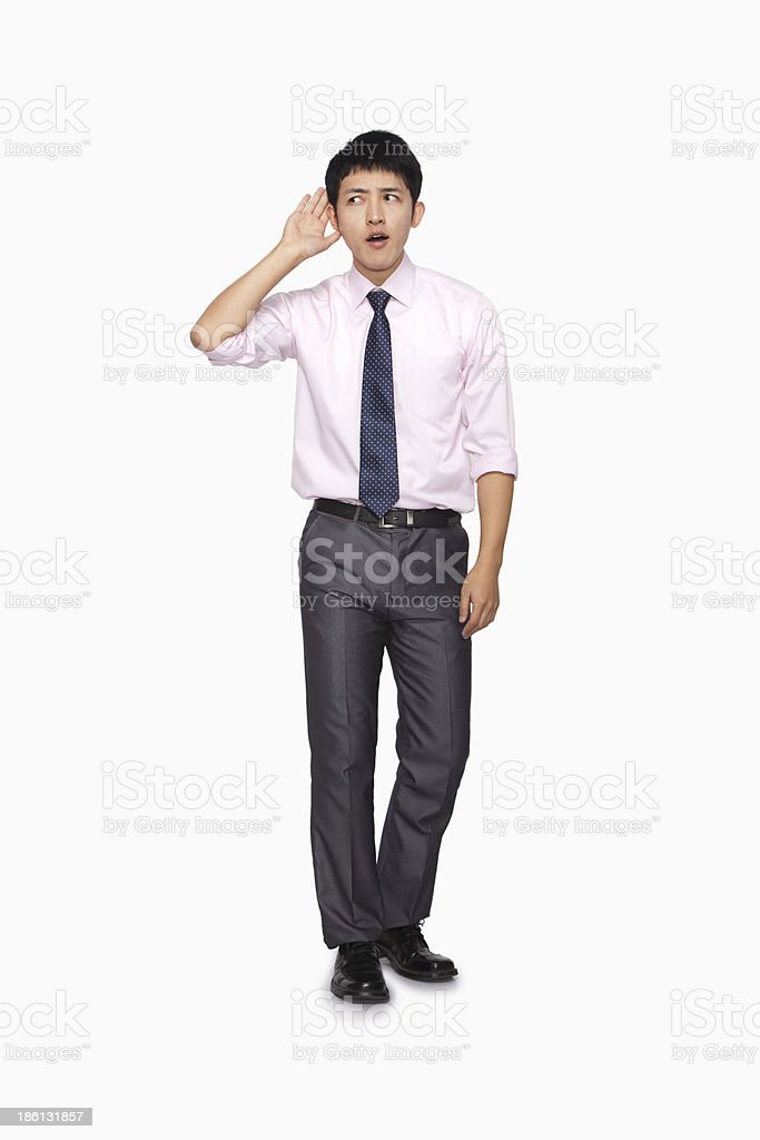 Businessman with hand on ear listening royalty-free stock photo
