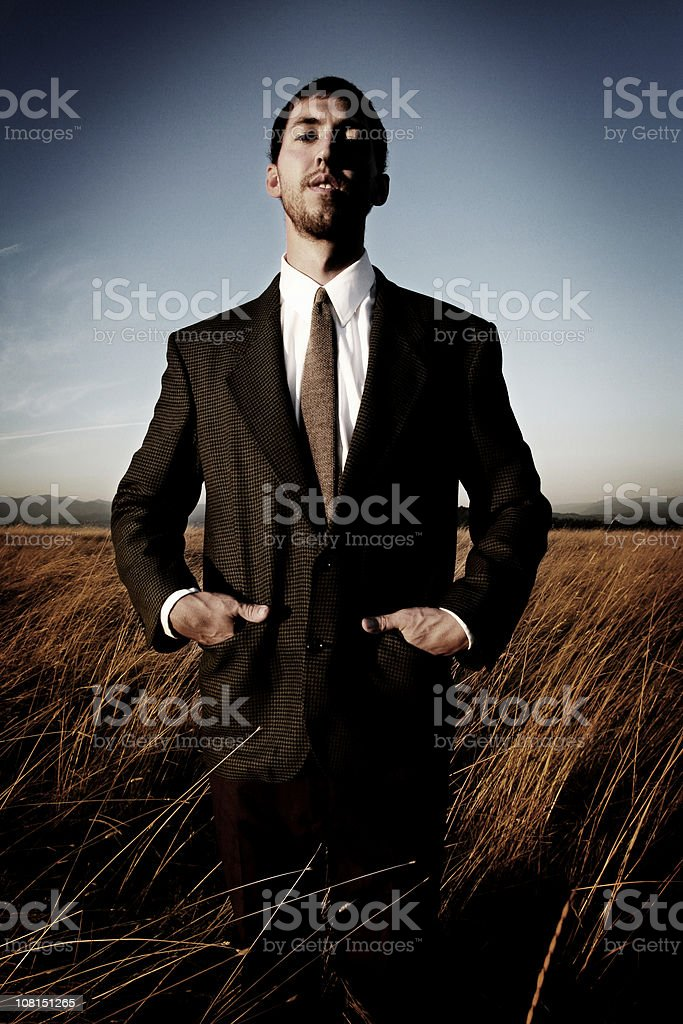 Businessman With Hands in Pockets Standing at Farm Field royalty-free stock photo