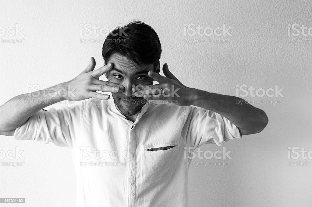 Businessman with hands over eyes look at camera stock photo
