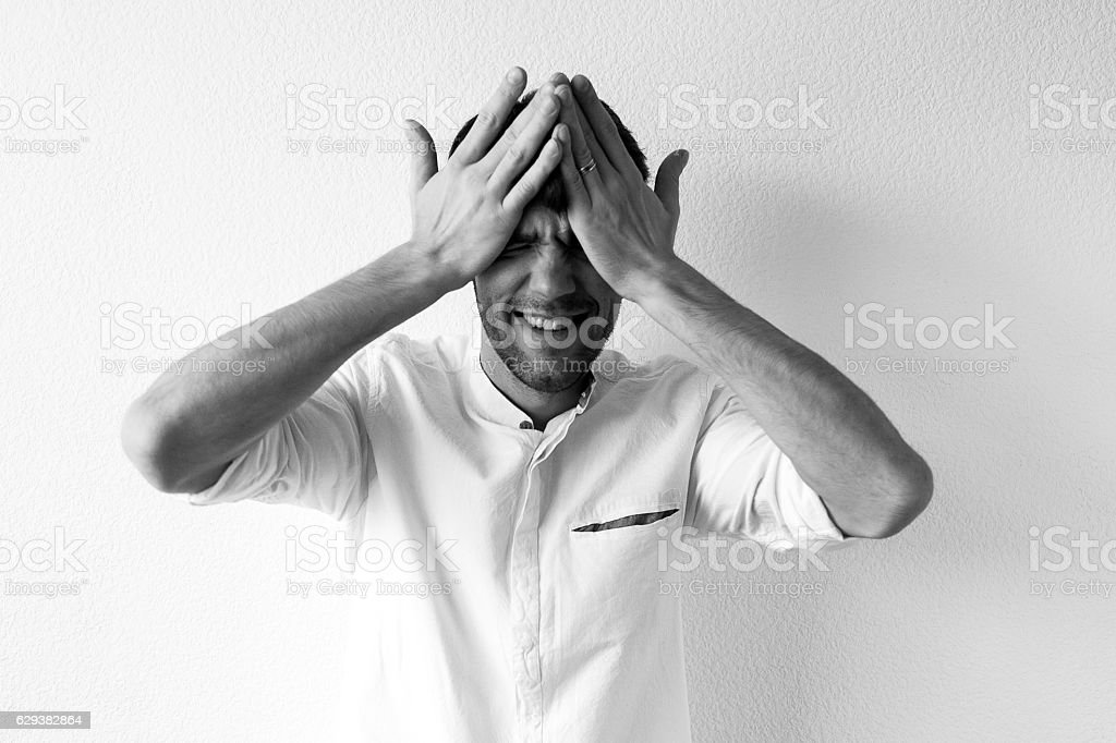 Businessman with hands over his eyes stock photo
