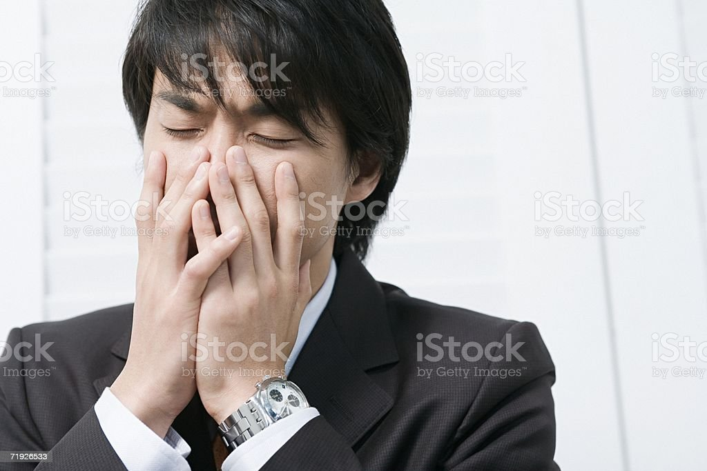 Businessman with hands over mouth stock photo