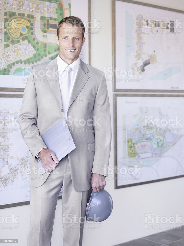 Businessman with hard hat in front of urban development plans royalty-free stock photo