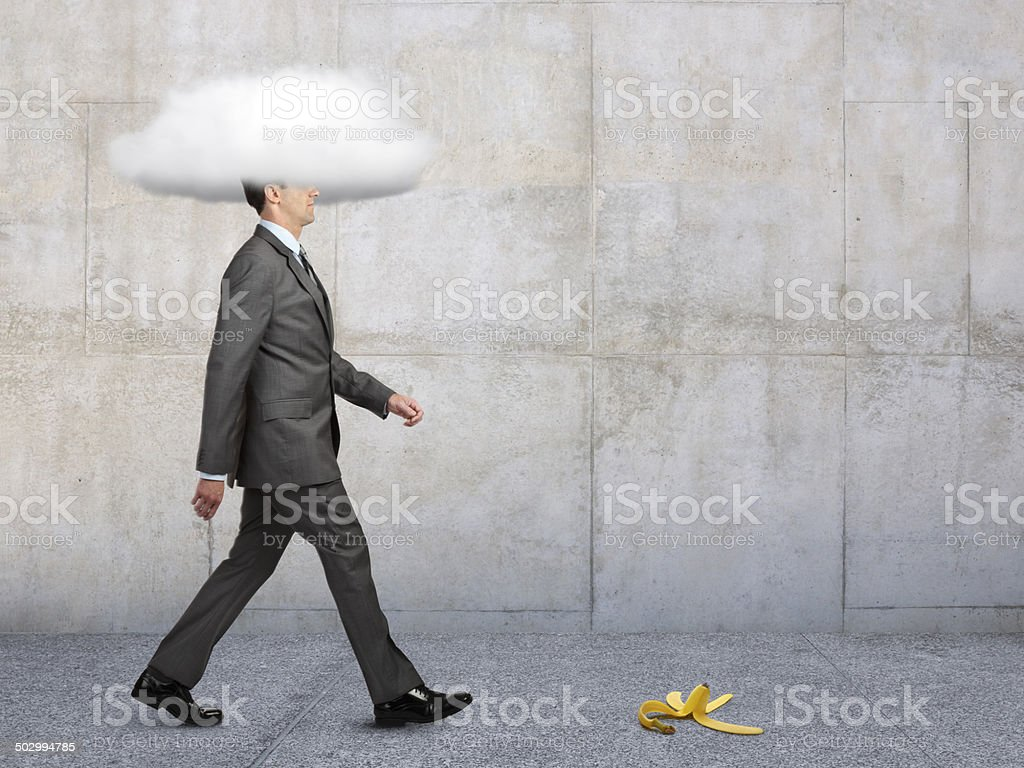 Businessman With Head In Clouds With Banana Peel In Path stock photo