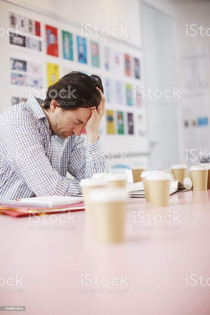 Businessman with head in hands surrounded by coffee cups in office royalty-free stock photo